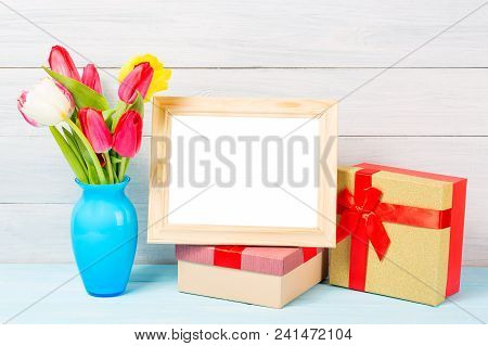Colorful Red Spring Tulip Flowers In Nice Blue Vase And Blank Photo Frame With Giftboxes On Light Wo