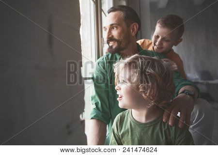 Outgoing Dad And Cheerful Kids Looking At Window While Sitting In Apartment