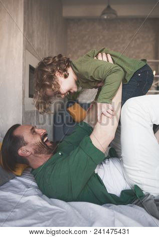 Side View Cheerful Dad Keeping Laughing Kid In Hands While Lying On Bed