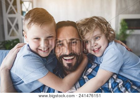 Portrait Of Cheerful Kids Embracing Happy Dad While Looking At Camera. Pleased Parent With Sons Conc