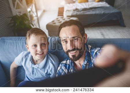 Portrait Of Beaming Man And Outgoing Kid Taking Selfie By Digital Device In Room