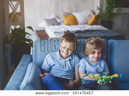 Portrait Of Happy Kid Playing Toy While Sitting Near Glad Brother. He Using Digital Device