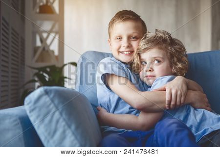 Portrait Of Happy Brother Embracing Pensive Kid While Sitting On Cozy Seat In Apartment