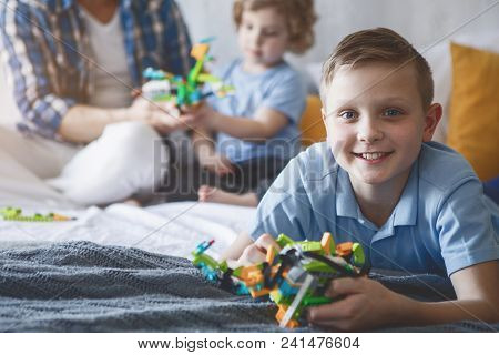 Portrait Of Cheerful Child Having Good Time With Toy Opposite Dad And Brother