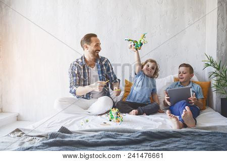 Full Length Outgoing Dad Playing With Cheerful Kids On Bed. Elder Brother Watching At Electronic Tab