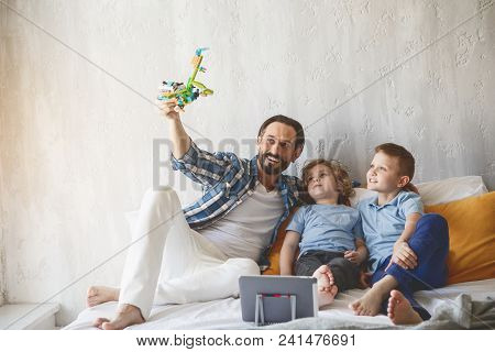 Full Length Portrait Of Cheerful Kids Having Good Time With Pleased Dad While Sitting On Bed