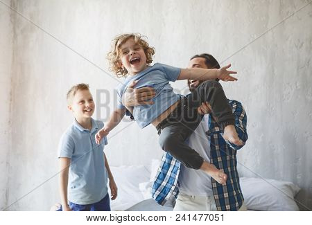 Outgoing Dad Throwing Up Beaming Child. Positive Older Brother Looking At Them. Optimistic Dad Havin