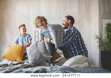 Outgoing Dad Having Fun With Two Little Sons While Sitting On Cozy Bed. Entertainment Concept