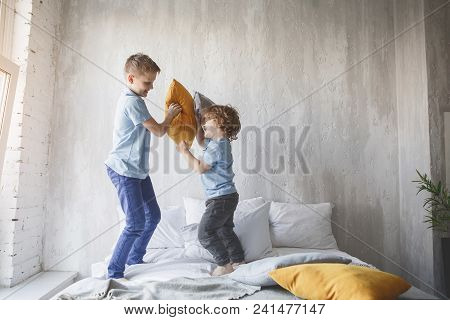 Full Length Side View Outgoing Boy Playing With Cheerful Little Brother With Cushions. Happy Boys Ha