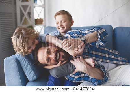 Portrait Of Smiling Father And Outgoing Sons Having Fun On Cozy Couch In Apartment. Happy Family Con