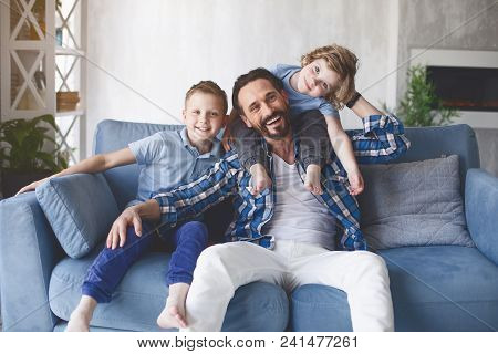 Portrait Of Outgoing Dad And Happy Kids Locating On Cozy Couch In Living Room. Positive Family Conce