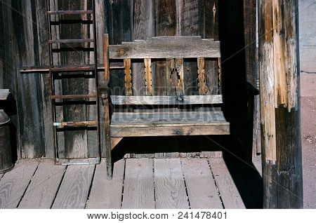 Old Rustic Wooden Bench On A Wooden Sidewalk, Bucolic