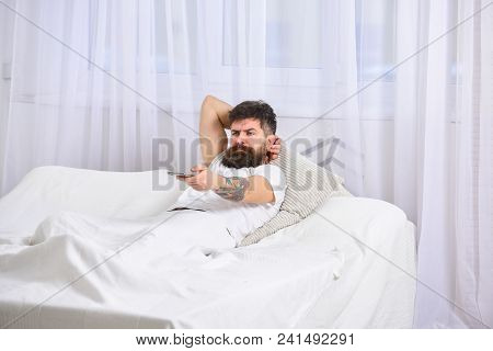 Man Laying On Bed, Watching Tv, White Curtains On Background. Guy On Serious Face Using Remote Contr