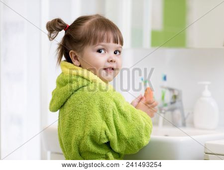 Side view of child little girl in green bathrobe washing her hands. poster