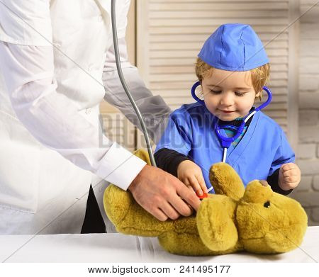 Male And Boys Hands Hold Stethoscopes On Wooden Background. Father And Kid With Interested Face Play