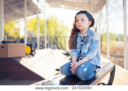 Little sad girl sitting lonely on a park bench