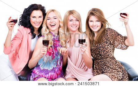 Portrait of young laughing happy women sitting on the couch with glasses of wine - isolated on white background.