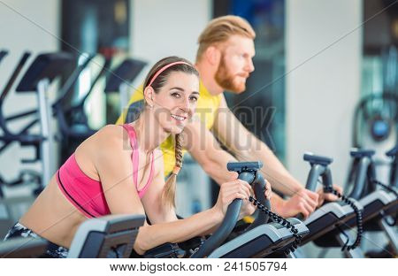 Portrait of a beautiful fit woman smiling while wearing pink fitness bra during routine on stationary bicycle at the gym