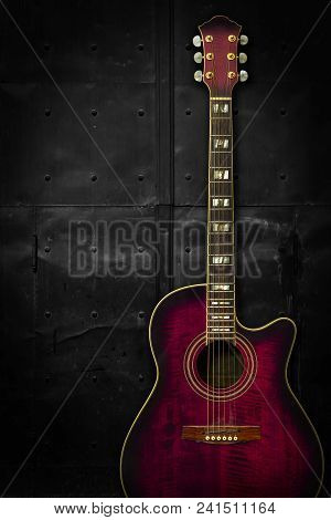 Photo Of A Purple Acoustic Guitar Leaning Up Against A Dark Metal Background.