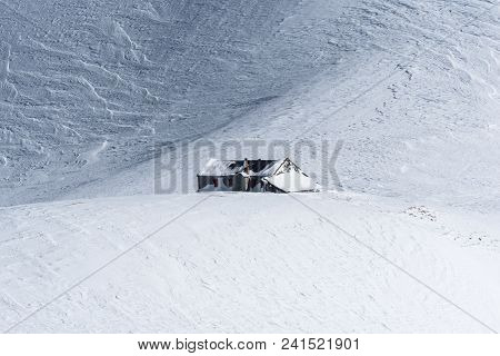 Mountain Hut In Vast Untracked Snow Field With Wavy Ridges Formed By Wind Packing The Snow On Sunny