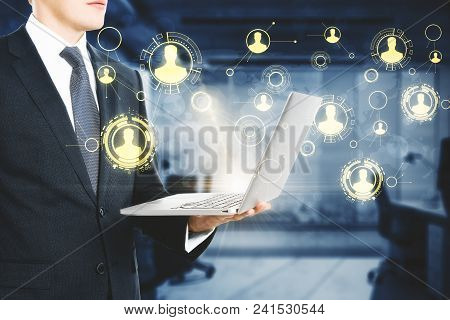 Businessman Using Laptop With Digital Business Interface In Blurry Office Interior. Technology And D