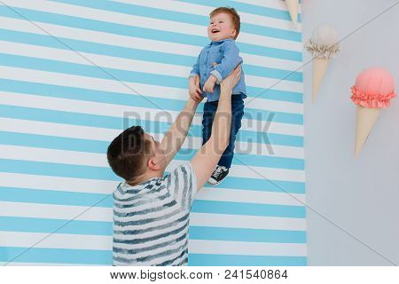 Father Raise His Little Son On His Hands On White And Blue Stripe Background. Playing In Babyroom.