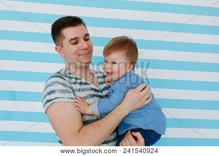 Young Father And Son Laughing On White Blue Stripe Background. Horizontal Close Portrait