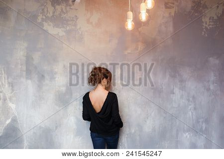 Woman Standing In Front Of Grungy Concrete Back To Camera. Loft Edison Lights Hanging From Ceiling.