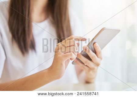 Woman Using Smartphone For The Application On Table In Room. Concepts For Digital Technology In Ever