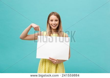Portrait Of Young Woman In Yellow Dress Pointing Finger At Side White Blank Board. Isolated Over Blu
