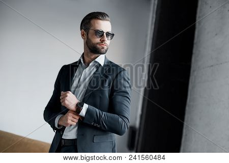 Young Bearded Stylish Businessman Leader Indoors At Office Wearing Sunglasses Walking Fixing Sleeves