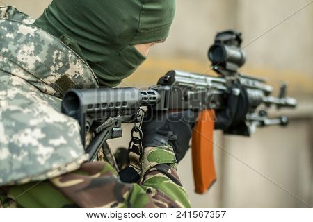 man aiming with an AK-47 with reflex sight poster