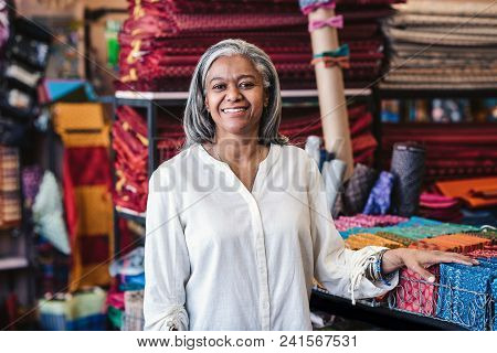 Portrait Of A Smiling Mature Fabric Store Owner Standing In Her Shop Surrounded By Racks And Shelves