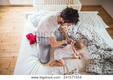 Father with a toddler girl on bed at home at bedtime. Paternity leave. poster