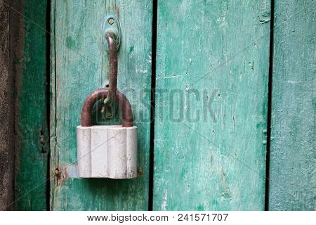 Vintage Door Handle With Hanging Lock, Closed Green Wood Door. Selective Focus Photo