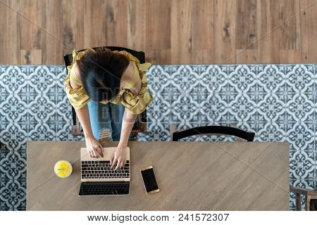 Top View Of Young Asian Woman Sitting, Using Laptop In Modern Workplace, Café Coffee Shop. Urban Fem