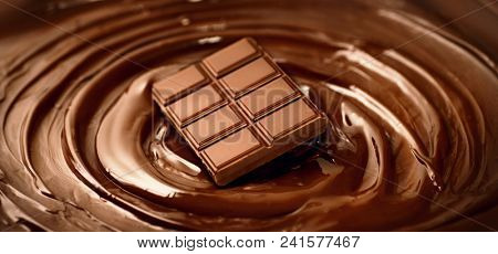 Chocolate. Bar of chocolate on melted liquid premium dark chocolate with a whisk. Close up of liquid hot swirl. Confectionery. confectioner prepares dessert