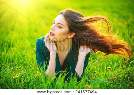 Beauty woman lying on the field with healthy long flying hair. Beautiful brunette Girl lying on the meadow. Enjoying nature. Spring or Summer Green Grass