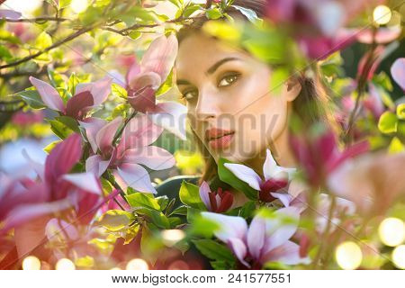 Beauty young woman enjoying nature in spring spring magnolia flowers. Beautiful brunette girl in Garden with blooming magnolia trees. Smiling girl with blossom flowers outdoors. Fashion model portrait