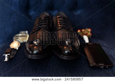 Accessories Of A Groom: Shoes, Boutonniere, Phone, Parfume And Clock On Dark Blue Textile Surface. W