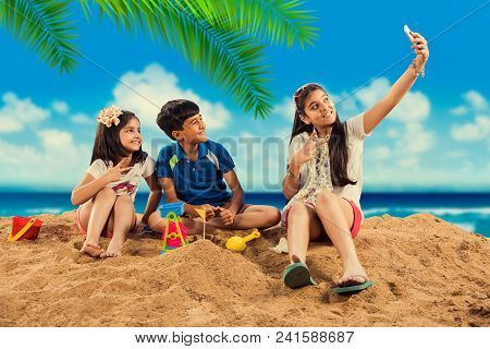 3 Indian/asian Kids Playing At Beach Sand