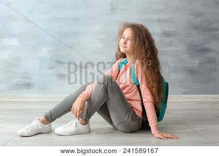 Stylish teenager with backpack sitting on floor near grey wall