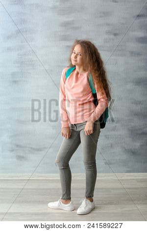 Stylish teenager with backpack near grey wall