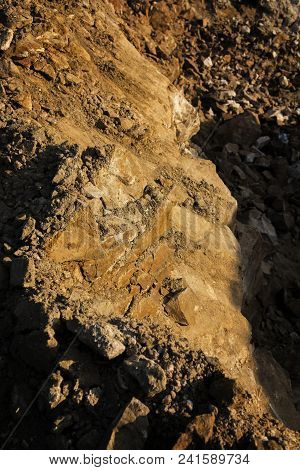 Fragment of a Stone quarry. Stone background. Stone. Quarry. Brown stone. Stone texture. Stone style. Grunge stone background. Nature grunge background.