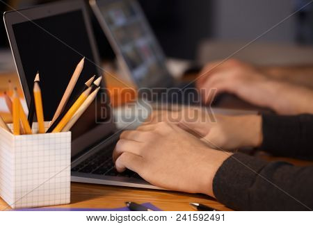 Male student with laptop doing homework at table, closeup