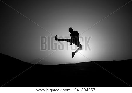 Silhouette Of Sportsman. Freedom, Energy Concept. Man Jump On Sunset Sky Background. Sport, Fitness,