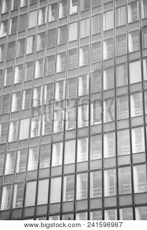 Glass Windows Of Office Building Exterior In Paris, France On Grey Facade Wall Background. Architect