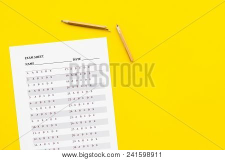 Exam Sheet On Yellow Table Flat Lay Space For Text. Education Concept.