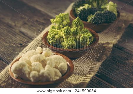 Fresh Pieces Of Romanesco Broccoli, Broccoli And Cauliflower In Small Rustic Wooden Bowls. Selective