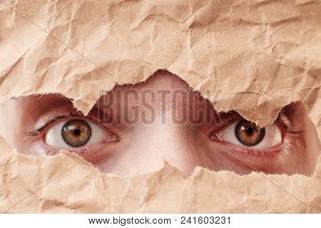 Eye Looking Through Hole In Paper. Spy Eye Watching Through A Hole. Eye Looking Through Hole In Old